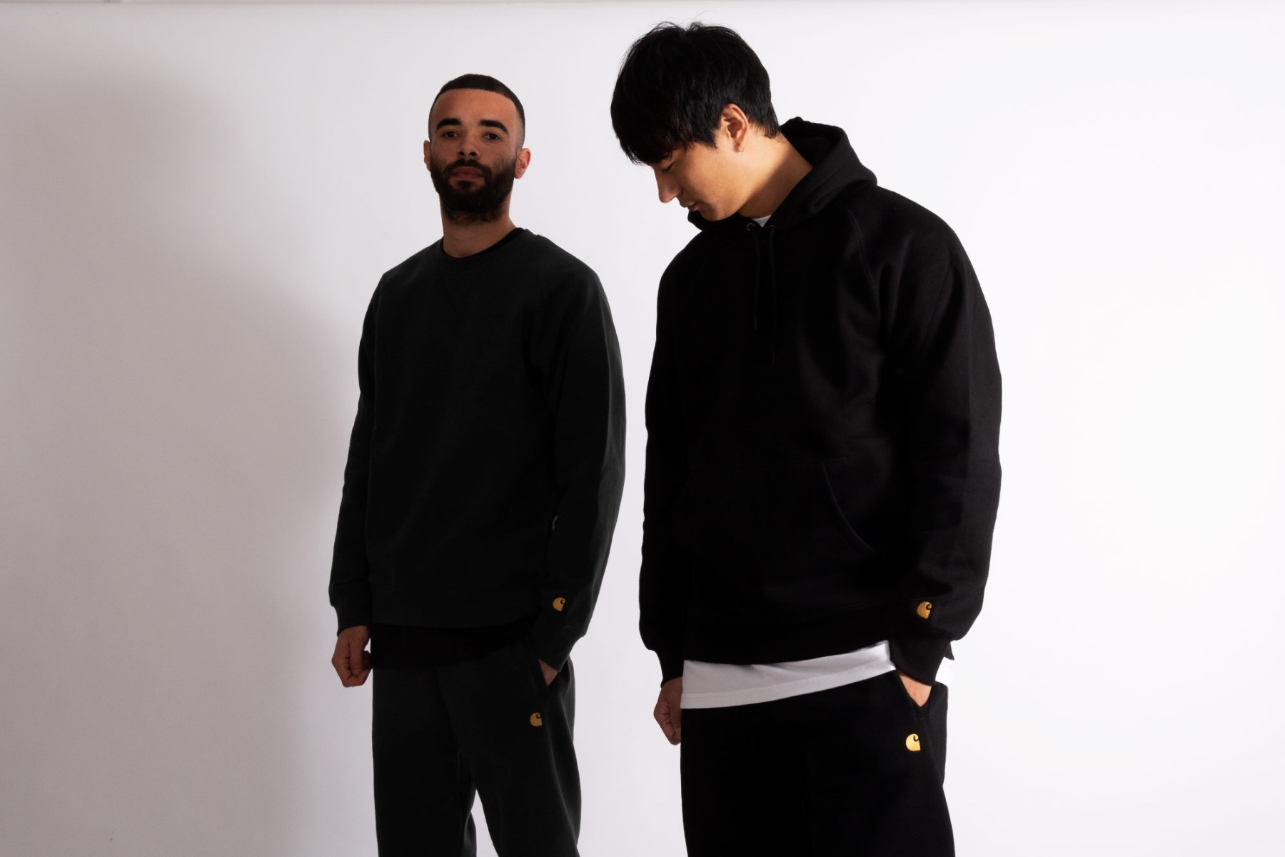 carhartt wip chase tracksuits in black/gold and dark teal